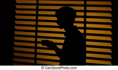 Man drinking coffee from a cup. Silhouette. Close up