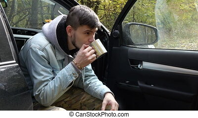 man drinking coffee in the forest