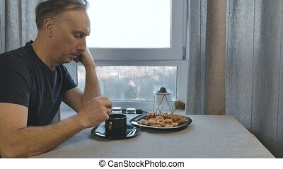 Man drinking coffee in the morning in the kitchen at home.