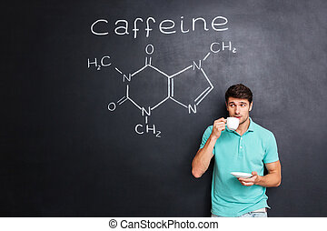 Man drinking coffee over blackboard with structure of caffeine molecule