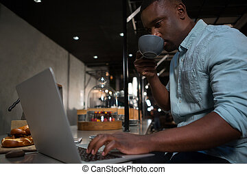 Man drinking coffee while using laptop at counter