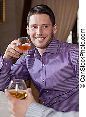 Man drinking cognac with friend - Man drinking cognac with...