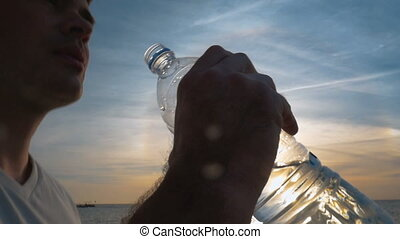 Man drinking fresh water from the bottle at sunset