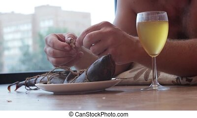 man drinking from a glass and eat fish, lying on the floor