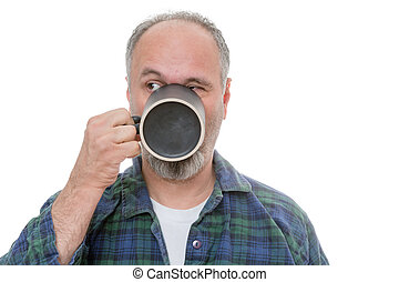 Man drinking from mug and looking over