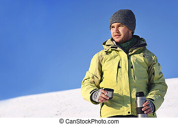 Man drinking hot coffee in thermos mug and looking into the mountains in snow, winter hike