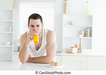 Man drinking orange juice in his kitchen