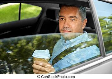 man drinking takeaway coffee on car back seat
