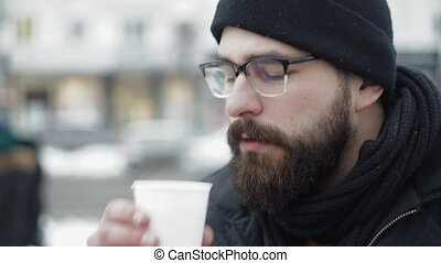Man drinking tea from white cup on winter city street