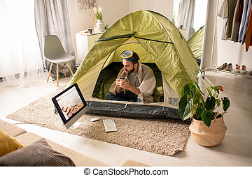 Man drinking tea in tent at home