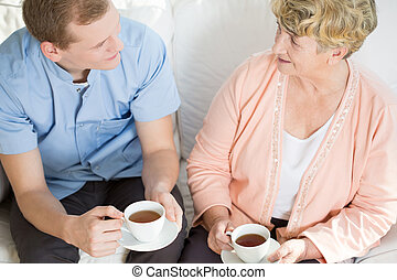 Man drinking tea with mature woman