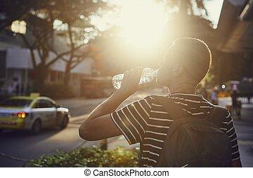 Man drinking water at sunset