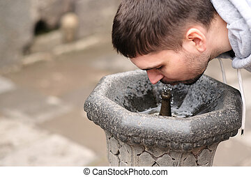 Man drinking water from fountain