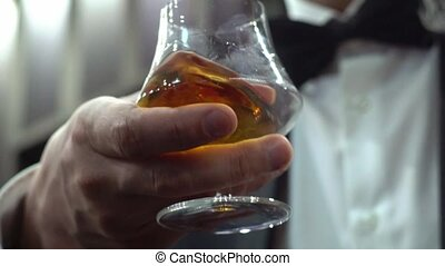 Man drinking whiskey. Holding glass
