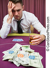 Man drinking whiskey looking stressed at poker table