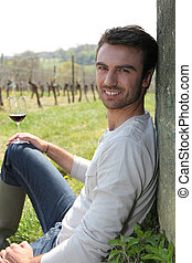 Man drinking wine in field