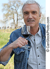 Man drinking wine in vineyard
