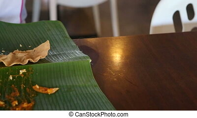 man drinks and eat food from banana leaf