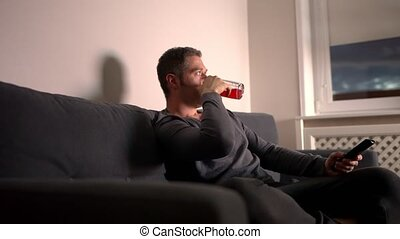Man drinks beer and watches a movie late at night.