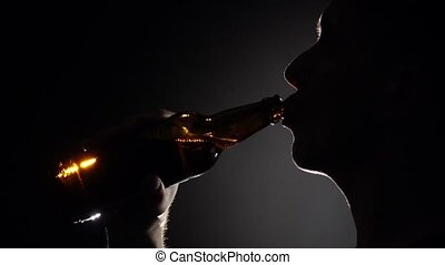 Man drinks beer from a bottle. Grey. Silhuoette. Close up. Slow motion