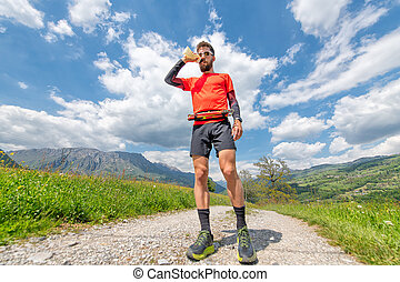 Man drinks from a water bottle during a trail in the mountains