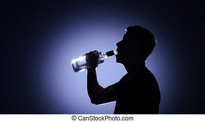 Man drinks vodka with throat. Back light