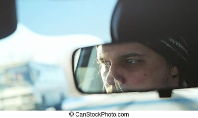 Man drivers the car in slow motion on winter landscape outdoors in sunny day. Close up of mirror inside the car.