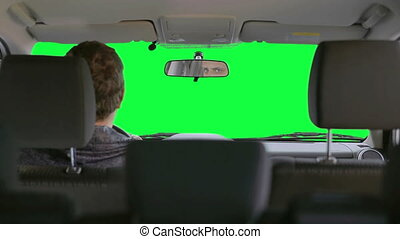 Man drives a car. Green background - The driver inside the...
