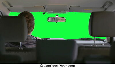 Man drives a car. Green background - The driver looking in...