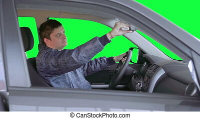 Man drives a car. Green background - The driver started the...