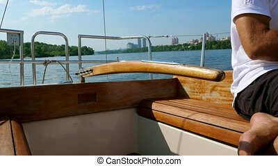 Man drives a small yacht on a river near the city.