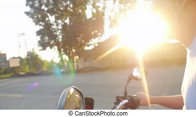 Man drives motorbike while traveling during beautiful sunset in slow motion. Vacation concept.