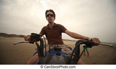Man Drives Quad At Beach