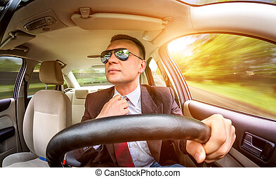 Man in a suit and sunglasses driving on a road in the car.