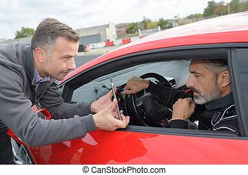 man driving a red car
