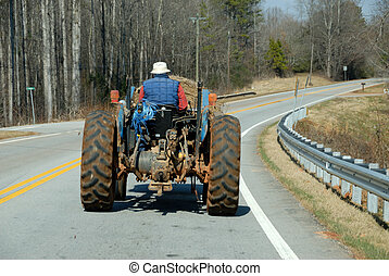 man driving a tractor view from front car window on main...