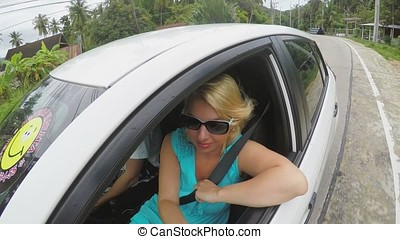 Man driving car and woman looks out of the car window