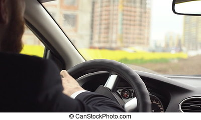 Man driving car on parking space, hands turning steering wheel, close up
