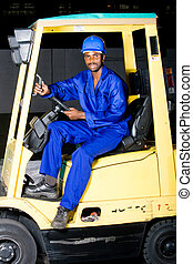 a man in overalls driving a forklift