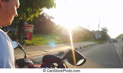 Man driving motorbike on tropical island while traveling during beautiful sunset in slow motion. Thailand. view of the steering wheel. 1920x1080