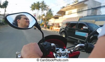 Man driving motorbike while traveling on tropical island...