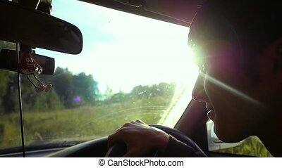 Man driving the car under sunset sky at outdoor in slowmotion. Summer time. 1920x1080
