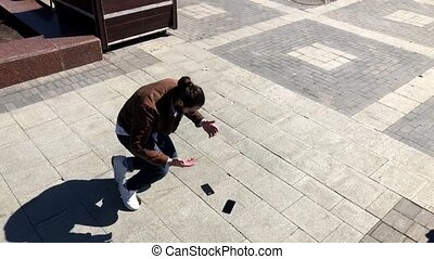 Man drops smartphone outdoors, slow motion