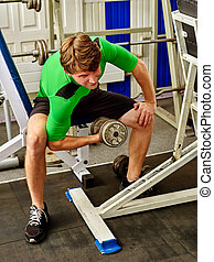 Man dumbell workout in gym. Muscle male working dumbbells body .