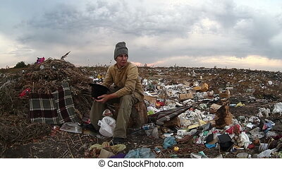 man dump unemployed homeless dirty looking food waste in...