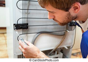 Man during fridge repair