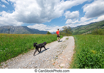 Man during walk in the mountains with his dog that follows him