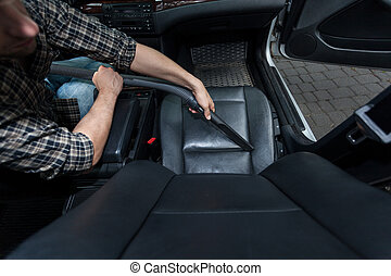Man dusting car's chair