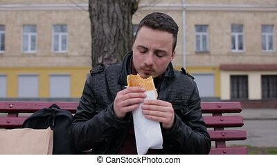 Man eat hotdog in the city on a bench - Young man eat hotdog...