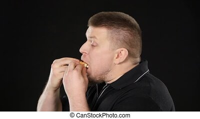 Man eating a cheeseburger. Black - Young man eating fast...